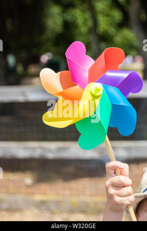 A hand holding up a childs milti coloured rainbow windmill - Stock Image