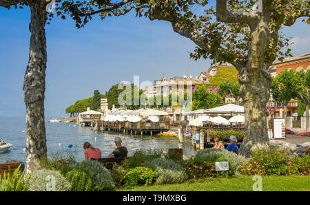 TORRI DEL BENACO, LAKE GARDA, ITALY - SEPTEMBER 2018: Scenic landscape view of  Torri del Benaco on Lake Garda framed by trees and branches. - Stock Image