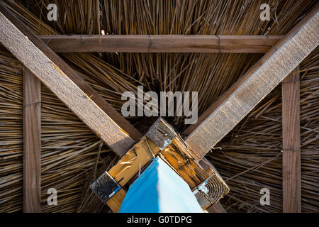 Wooden sunshade, straw umbrella with a blue foot, view from below - Stock Image