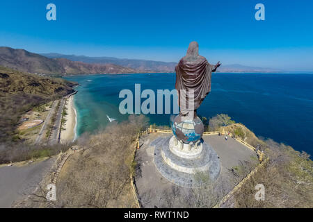 Aerial view of Cristo Rei of Dili, high statue of Jesus Christ located atop a globe in Dili city, East Timor, on a summit, overlooking the capital of  - Stock Image