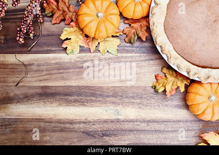Homemade pumpkin pie in pie plate with little pumpkins, autumn leaves and room for text over rustic wooden background. Image shot from overhead. - Stock Image