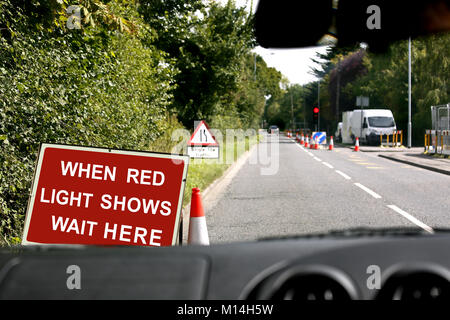 A view through the windscreen of a vehicle waiting at a red roadworks traffic light - Stock Image