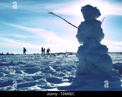 Rest of real snowman in outdoor winter white scenery,people in background. - Stock Image