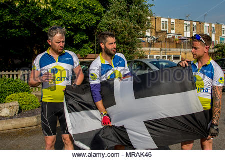 Hook, Hampshire, UK. 26th May 2018. Cancer patient and father of three Gareth Lancaster (40) and a team of cyclist from Cornwall are riding 240 miles of the Trafalgar Way from Launceston to Admiralty Arch, London to raise funds for Sarcoma UK. Over £13k has already been pledged. Despite major surgery last year in Birmingham Orthopaedic Hospital to remove a tumour and much of the front of his pelvis, Gareth's cancer has returned and he will require further surgery after the ride. Photo: Gareth (centre) with the Cornish flag and two teammates. Credit: Images by Russell/Alamy Live News - Stock Image