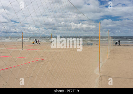 Walkers with strollers family on the beach Sea - Stock Image