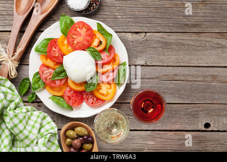 Caprese salad with tomatoes, basil and mozzarella. With rose and white wine. Top view with space for your text - Stock Image