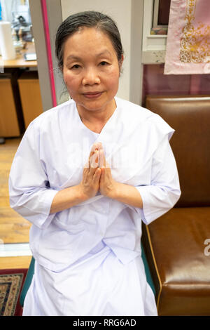 Posed portrait of a Buddhist nun in white clothing at a prayer service at a temple in Elmhurst, Queens, New York City. - Stock Image