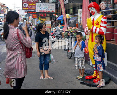 Thailand mother photographing her children with Ronald McDonald and all adopting the Thai traditional greeting known as Wai - Stock Image