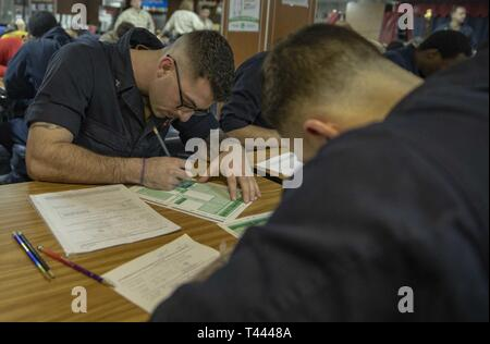 U.S. 5TH FLEET AREA OF OPERATIONS (March 14, 2019) Air Traffic Controlman 3rd Class Robert Wyker takes the Navywide petty officer second class advancement exam on the mess deck of the Wasp-class amphibious assault ship USS Kearsarge (LHD 3). Kearsarge is the flagship for the Kearsarge Amphibious Ready Group and, with the embarked 22nd Marine Expeditionary Unit, is deployed to the U.S. 5th Fleet area of operations in support of naval operations to ensure maritime stability and security in the Central Region, connecting the Mediterranean and the Pacific through the western Indian Ocean and three - Stock Image
