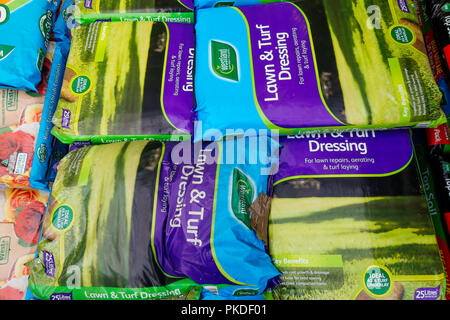 A stack of bags of Westland Lawn and Turf Dressing for feeding grass and killing moss  in a garden centre - Stock Image