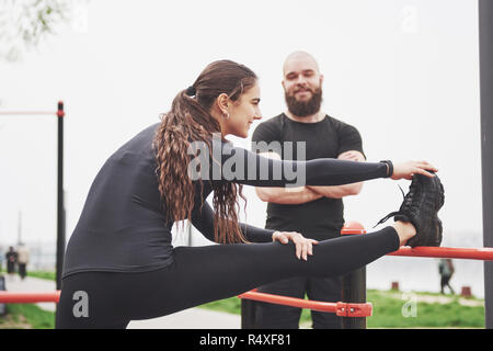 Young man and woman perform exercises and stretch marks before doing sports - Stock Image