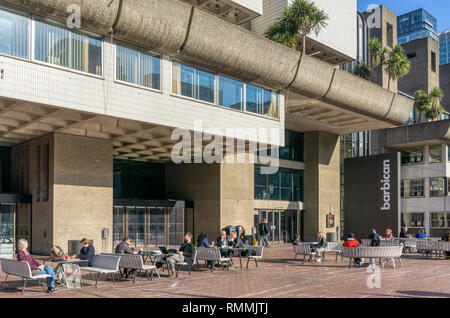 People sitting outside the Barbican. - Stock Image