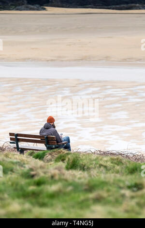 A man sitting alone on a bench overlooking a deserted Crantock Beach in Newquay in Cornwall. - Stock Image