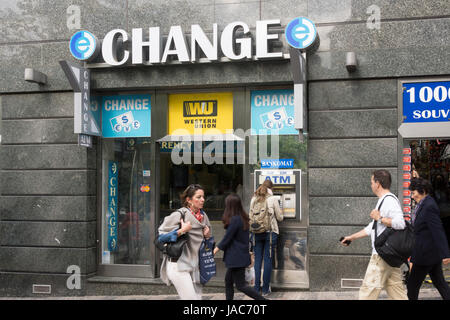 A person withdrawing cash from an ATM at a Western Union bureau de change / currency exchange in Prague, Czech Republic - Stock Image