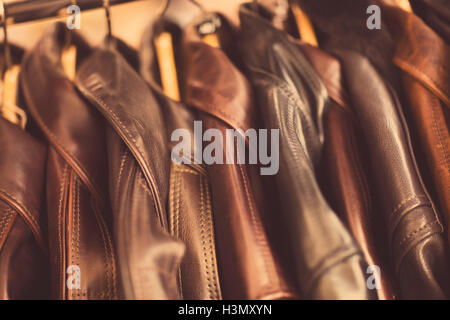 Leather jackets hanging in a row, in leather jacket manufacturers, close-up - Stock Image