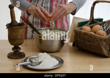 Woman baking a cake, adding an egg to a bowl, surrounded by the other ingredients. - Stock Image