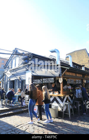 Food stalls on vibrant Camden Market in the spring sunshine, in north London, UK - Stock Image