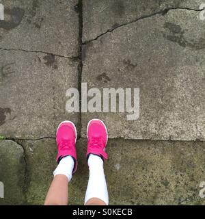 Youth, school children concept. Pink trainers with knee socks on a 7 year old girl. - Stock Image