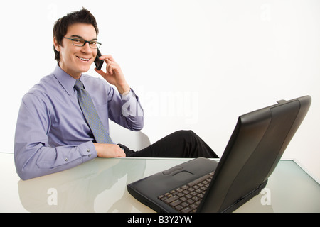 Smiling Asian businessman sitting at desk talking on cellphone - Stock Image