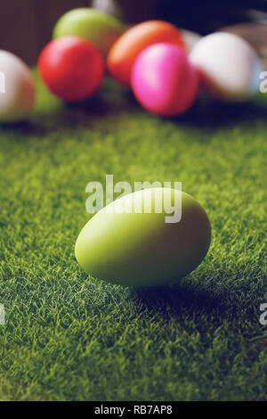 A beautiful and colorful close-up of green easter egg over green grass and an amazing bokeh of many eggs in different colors as background - Stock Image