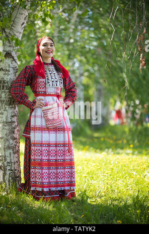 Young woman in traditional russian clothes standing in the forest and holds hands on a waist - vertical shot - Stock Image