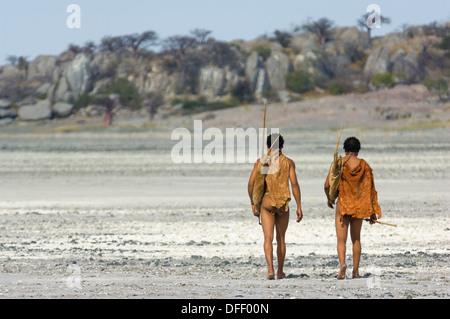 San bushman trackers walking across the cracked pan towards the ancient granite outcrop of Kubu Island (Lekhubu), Makgadikgadi Pan, Botswana - Stock Image