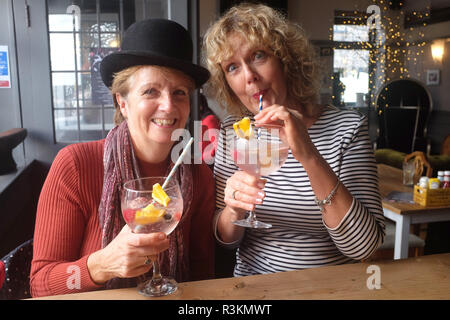 Women one wearing a bowler hat in the Cobb Arms  drinking a large gin and tonic with paper straws UK - Stock Image