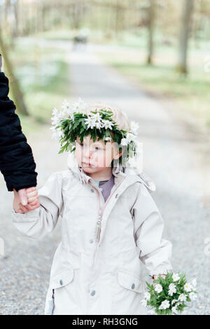 Girl wearing anemone wreath holding parents hand - Stock Image