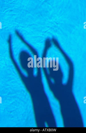 shadows of 2 young sisters with arms raised in swimming pool water - Stock Image