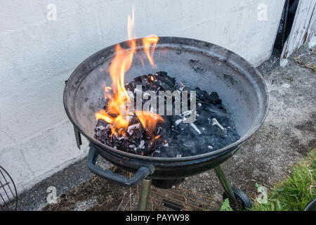 Charcoal burning in a barbecue in readiness to cook. - Stock Image