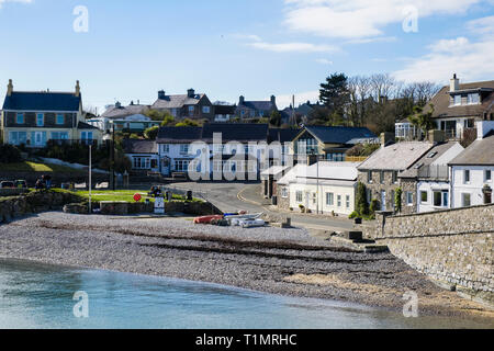 View across beach to cottages and pub on waterfront in village of Moelfre, Isle of Anglesey, Wales, UK, Britain - Stock Image