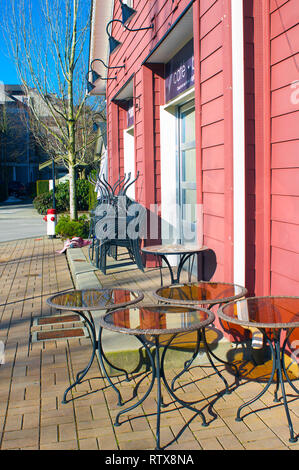 Side view of building showing outdoor tables and stacked chairs on the patio. - Stock Image