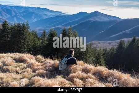 One man hiker wearing vintage rucksack sitting alone admiring the mountain landscape in winter. - Stock Image