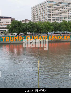 Westminster, London, 12th July 2018. Campaigners against climate change protest over Donald Trump's visit by dropping a giant banner reading 'Trump: Climate Genocide' at St Thomas' Hospital Gardens, opposite the Houses of Parliament in Westminster. The huge banner, 100 metres x 9 metres large, is to raise awareness about the US president's climate policies. Credit: Imageplotter News and Sports/Alamy Live News - Stock Image