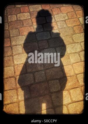 Shadow silhouette selfie with thick winter coat and hat, over brick pavement, with vintage sandstone texture overlay - Stock Image