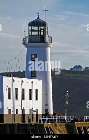 Scarborough's Diving Belle statue stands dwarfed alongside the town's lighthouse at the harbour entrance, against the backdrop of Holbeck's cliffs. - Stock Image
