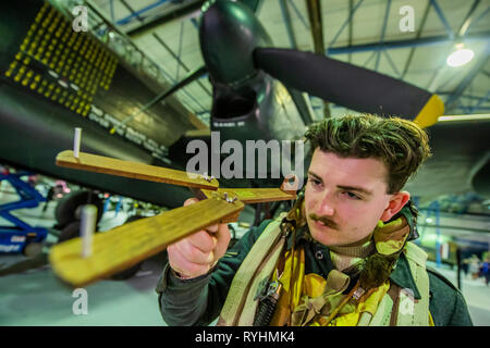 London, UK. 14th March, 2019. A re-enactor with a replica of the Dambuster aiming device in front of the Lancaster - Immersive Histories: Dambusters Virtual Reality Experience. An opportunity to step back in time to the early hours of 17 May 1943 and on board Avro Lancaster G-George to join the Dambusters on their legendary mission. Using the latest virtual reality and haptic technology, in conjunction with a physical 1:1 recreation of the interior of the iconic Avro Lancaster bomber. Credit: Guy Bell/Alamy Live News Credit: Guy Bell/Alamy Live News - Stock Image