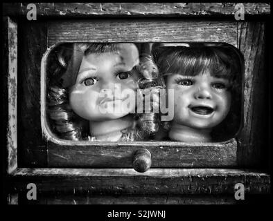 Two dolls heads enclosed in a wooden container. Where's the rest of their bodies? Weird, funny or just plain grotesque? An image with a message? Photo Credit - © COLIN HOSKINS. - Stock Image