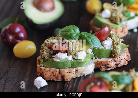 Avocado toast sandwich with avocados, pesto, feta cheese, fresh from the garden basil and heirloom tomatoes, over a rustic wooden background. Greek fo - Stock Image