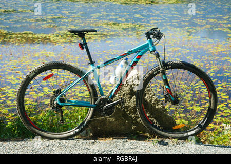 Rocky Mountain hard tail bike parked on the edge of a pond. - Stock Image