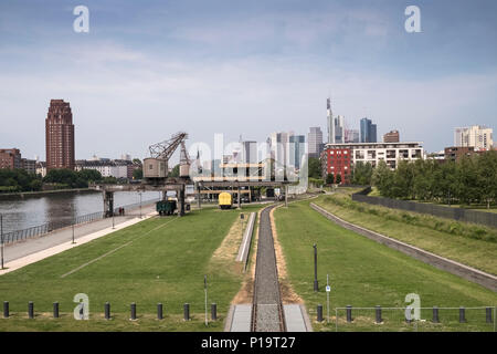 Industrial heritage artefacts alongside the river Main, with modern architecture skyline in the background, Ostend, Frankfurt am Main, Hesse, Germany. - Stock Image