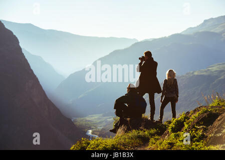 Group of three friends in mountains range - Stock Image