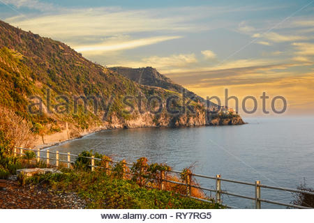 The coast of Cinque Terre Italy and the Ligurian Sea, with the village of Corniglia in the distance as the sun sets in early Autumn - Stock Image