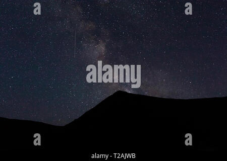 Silhouette of mountain at night - Stock Image