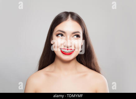Pretty woman in braces smiling on white - Stock Image