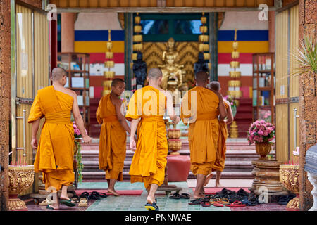 A group of young Buddhist monks wearing orange robes walking towards a shrine before their evening prayers in Phnom Penh, Cambodia. - Stock Image