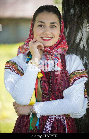 Young woman in traditional russian clothes standing under a tree and holds hand at face - looking to camera - vertical shot - Stock Image