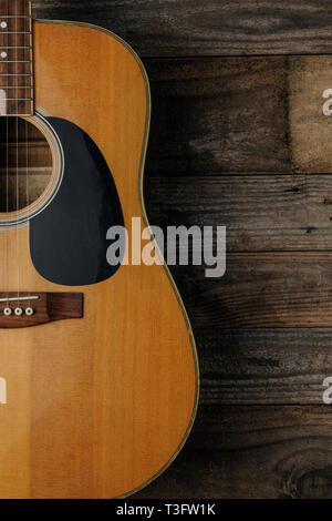 Acoustic guitar on grunge wood background to use as book cover for a guitar course - Stock Image