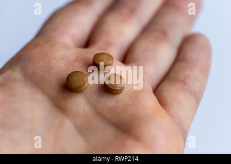 Three ferrous fumerate brown iron tablets inside of a hand - Stock Image
