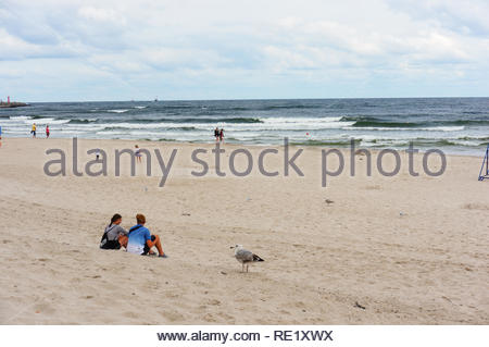 Kolobrzeg, Poland - August 10, 2018: Couple sitting on sand and looking at the sea. It is a rainy day in the high season at the seaside. Because of th - Stock Image